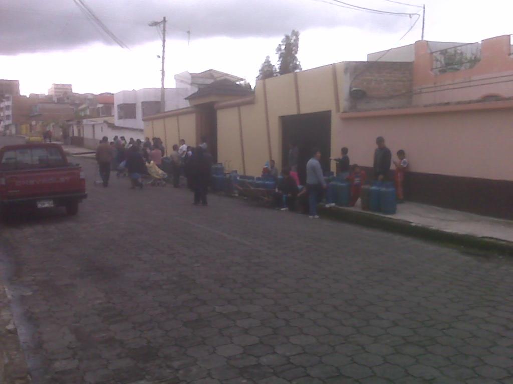 Fila (de las pequeñas) de gente a la espera del carro repartidor de gas.